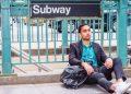 Man-sitting-under-subway-sign-wearing-earbuds